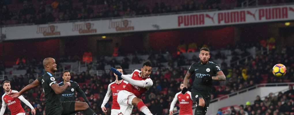 LONDON, ENGLAND - MARCH 01:  Pierre-Emerick Aubameyang of Arsenal shoots under pressure from Vincent Kompany and Nicolas Otamendi of Man City during the Premier League match between Arsenal and Manchester City at Emirates Stadium on March 1, 2018 in London, England.  (Photo by David Price/Arsenal FC via Getty Images) *** Local Caption *** Pierre-Emerick Aubameyang;Nicolas Otamendi;Vincent Kompany