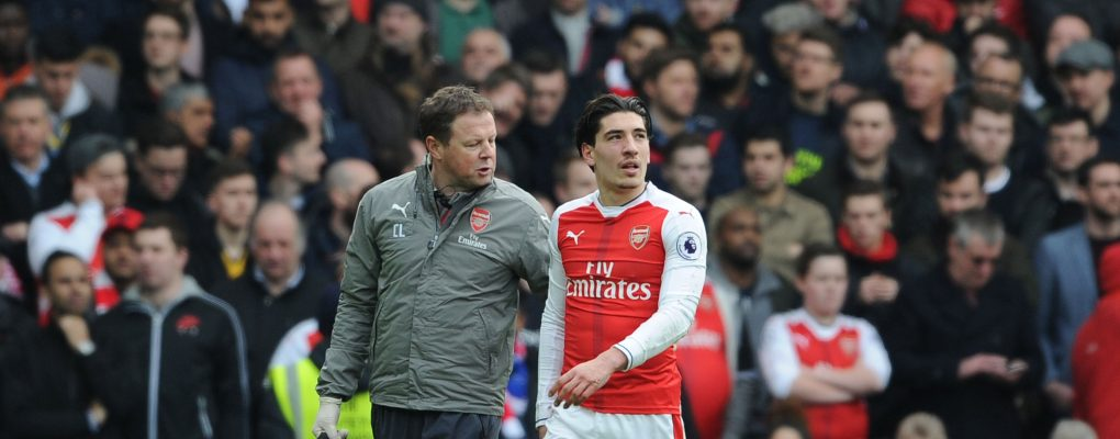LONDON, ENGLAND - FEBRUARY 04: Injured Arsenal defender Hector Bellerin is led from the pitch by physio Colin Lewin during the Premier League match between Chelsea and Arsenal at Stamford Bridge on February 4, 2017 in London, England. (Photo by Stuart MacFarlane/Arsenal FC via Getty Images) *** Local Caption *** Hector Bellerin;Colin Lewin
