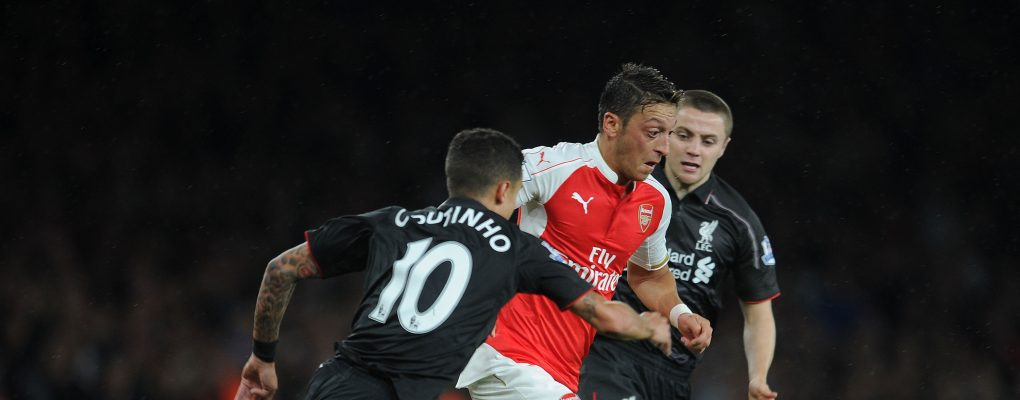 LONDON, ENGLAND - AUGUST 24:  Mesut Ozil of Arsenal burts between Countinho and Jordan Rossiter of Liverpool during the Barclays Premier League match between Arsenal and Liverpool on August 24, 2015 in London, United Kingdom.  (Photo by David Price/Arsenal FC via Getty Images) *** Local Caption *** Mesut Ozil; Oezil; Countinho; Jordan Rossiter