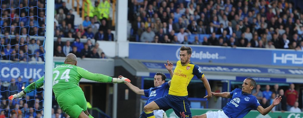 LIVERPOOL, ENGLAND - AUGUST 23:  Aaron Ramsey holds off Evertons (L) Leighton Baines and (R) Leon Osman to score Arsenal's 2nd goal past goalkeeper Tim Howard during the Barclays Premier League match between Everton and Arsenal at Goodison Park on August 23, 2014 in Liverpool, England.  (Photo by Stuart MacFarlane/Arsenal FC via Getty Images) *** Local Caption *** Aaron Ramsey;Leighton Baines;Leon Osman;Tim Howard
